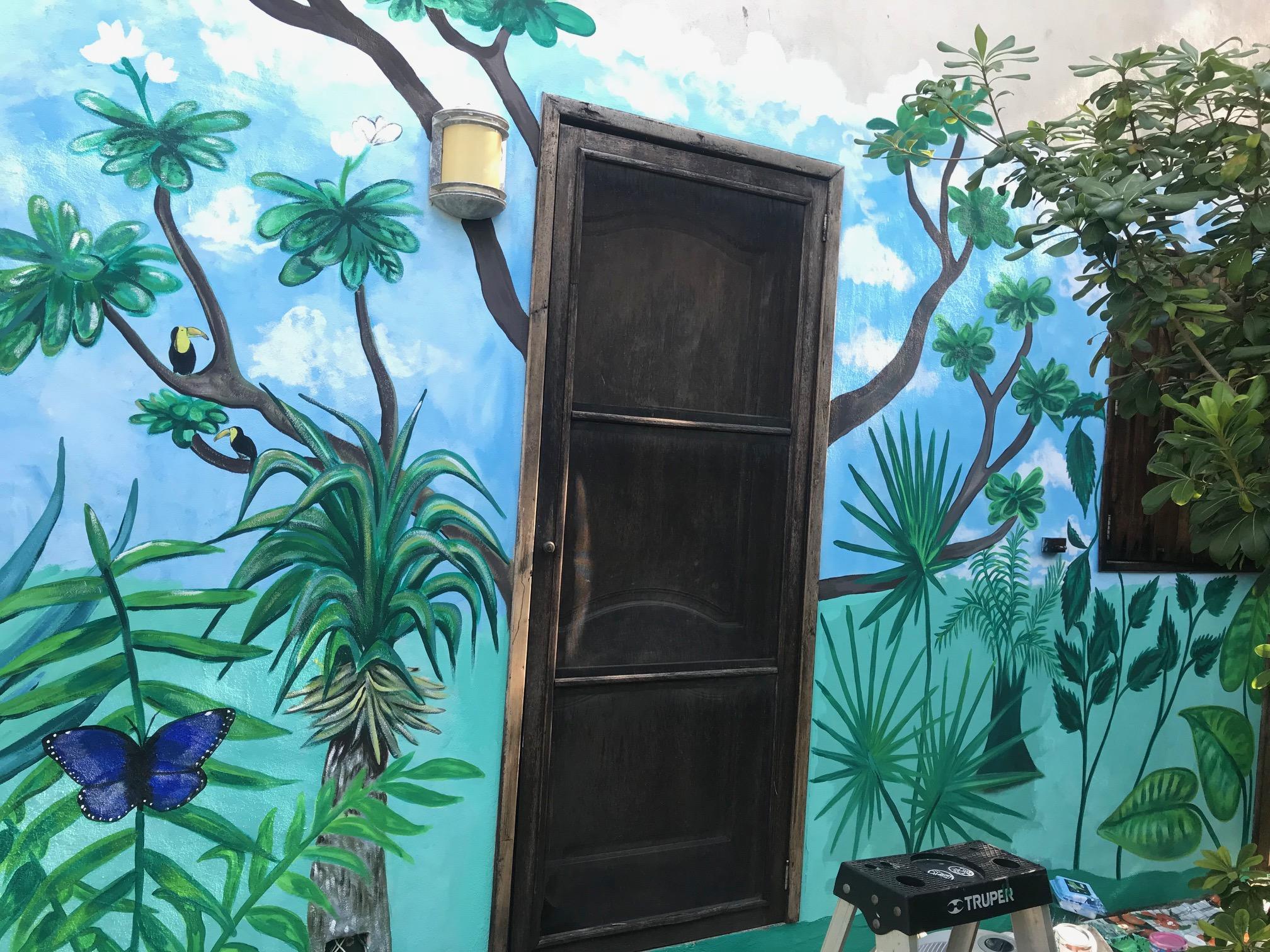 tropical mural surrounding a door