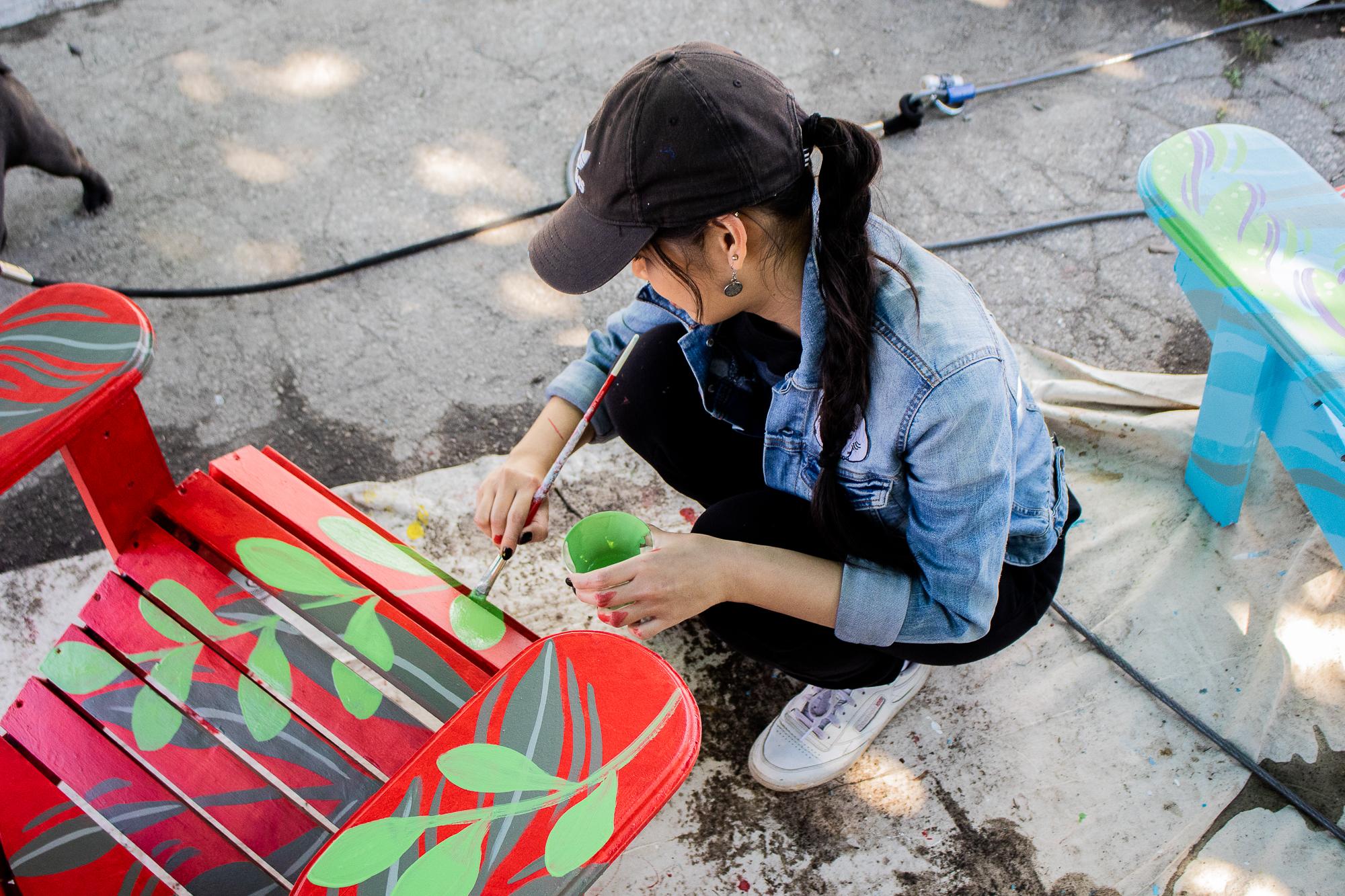 Katrina Canedo painting a red muskoka chair with green plants